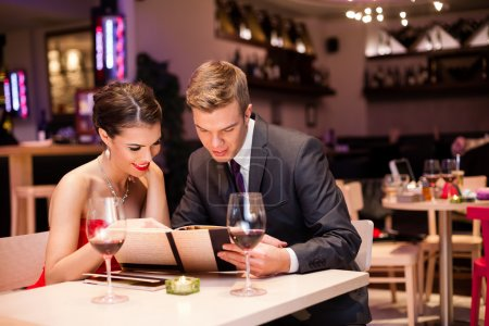 Photo for Smiling couple reading menu and choosing meal - Royalty Free Image