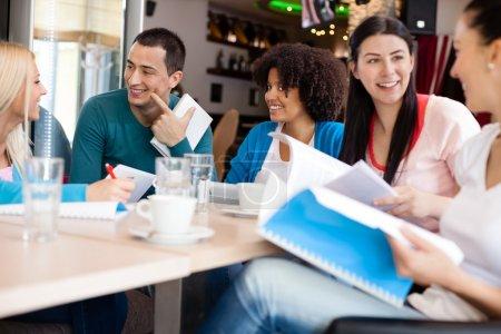 Photo pour Jeunes étudiants discutant au café - image libre de droit