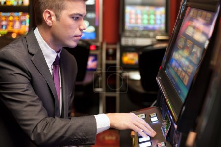 Men gambling in the casino on slot machines