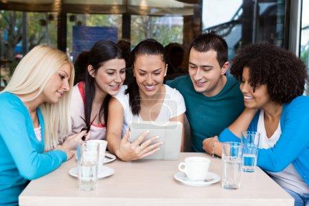 Photo pour Groupe d'adolescents dans le café en utilisant une tablette numérique - image libre de droit