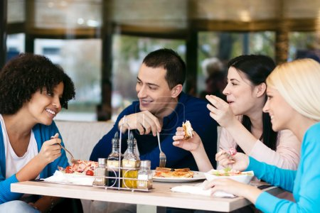 Photo for Four cheerful friends chatting while lunch in restaurant - Royalty Free Image