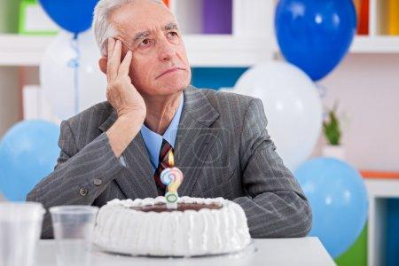 Photo pour Les hommes âgés assis avant d'anniversaire gâteau demandent quel âge je suis - image libre de droit