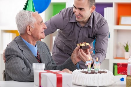 Smiling senior man receiving gift for birthday