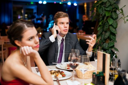 Photo for Man talking on a cell phone while on a date with his girlfriend or wife - Royalty Free Image