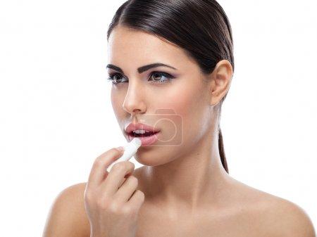 Photo pour Femme appliquant du baume sur les lèvres - image libre de droit