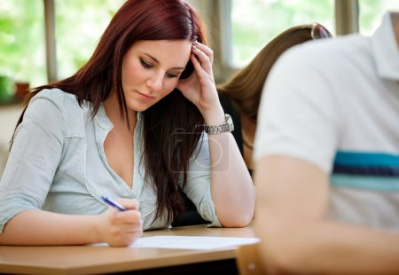 Photo for Young concentration student girl doing test in class - Royalty Free Image