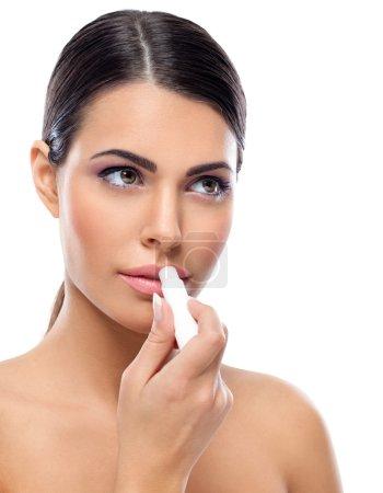 Photo pour Jeune femme appliquant du baume sur les lèvres - image libre de droit
