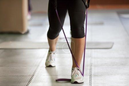 Photo pour Exercice avec une bande de résistance, gros plan des pieds féminins - image libre de droit