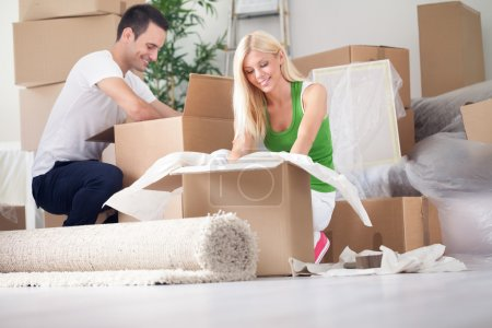 young couple unpacking or packing boxes