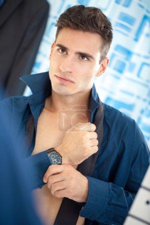Businessman getting dressed in bathroom