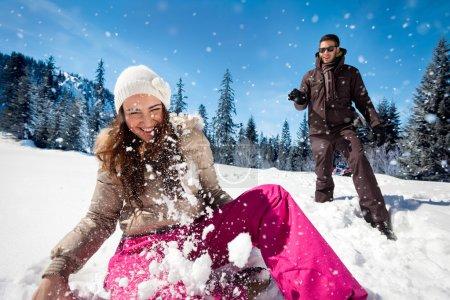 Photo pour Jeune couple jouant dans la neige, vu le combat de boule de neige - image libre de droit