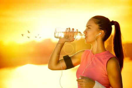 Photo for Sporty woman drinking water outdoor on sunny day - Royalty Free Image