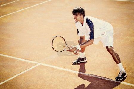 Photo pour Jeune homme jouer au tennis en plein air sur un court de tennis orange - image libre de droit