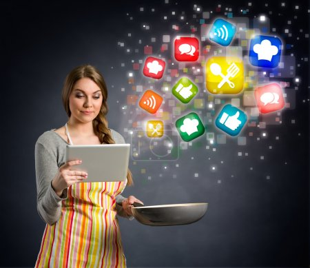 Photo for Young woman cooking using the tablet, cloud of colorful social media icons out of tablet pc - Royalty Free Image
