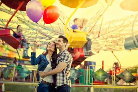 Jeune couple étreignant dans le parc d'attractions