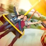 Young happy couple having fun at amusement park, r...