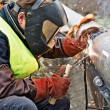 Welder wearing protective clothing for welding ind...