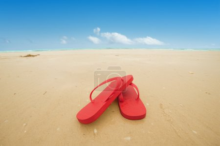Photo for Red flip flops on the beach sand.Concept of summer vacations - Royalty Free Image