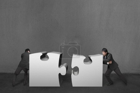 Businessmen push two heavy puzzles together in concrete wall bac