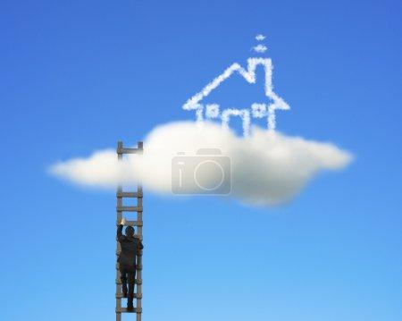 Businessman climbing on wooden ladder to reach cloud house