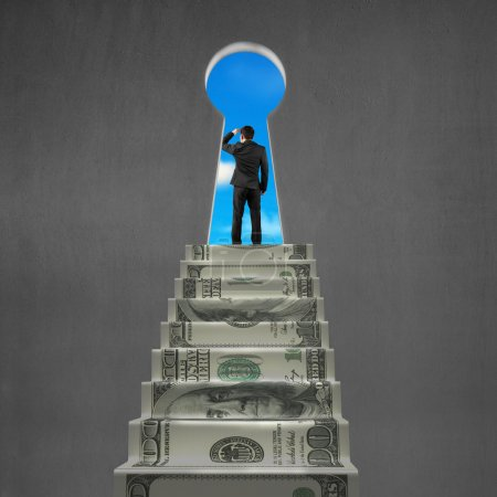 Man looking on top of money stairs with key hole