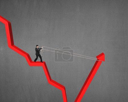 Photo pour Homme tirant vers le haut descendant flèche rouge fond de mur en béton - image libre de droit