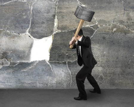 Photo for Businessman holding sedgehammer to crack concret wall - Royalty Free Image