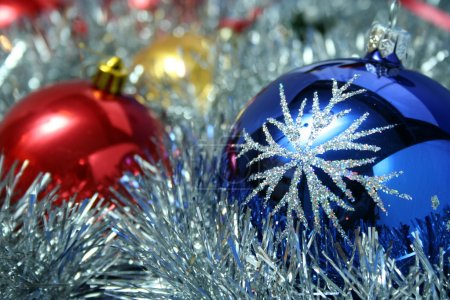 Photo for Three christmas glass spheres of dark blue, yellow and red color with a pattern on a background of a New Year's tinsel, (look similar images in my portfolio) - Royalty Free Image