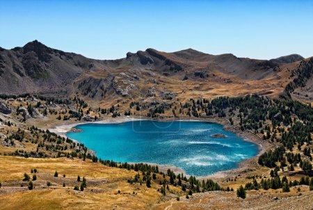Photo pour Image du lac d'Allos (2228 m) lors d'une journée venteuse avec des reflets de lumière solaire sur la surface de l'eau ondulée. Ce lac est le plus grand lac naturel (54 ha) en Europe à - image libre de droit
