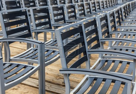 Photo for Row of wet chairs on a wooden floor located outdoors in a rainy day. - Royalty Free Image