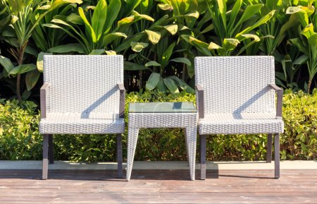 Photo pour Fauteuils en rotin mobilier d'extérieur et table sur la terrasse dans un beau jardin. - image libre de droit