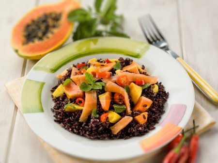 black rice with papaya and smoked salmon, selective focus