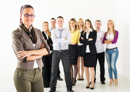 Photo for Smiling businesswoman standing in front of colleagues with crossed arm and looking at the camera. - Royalty Free Image