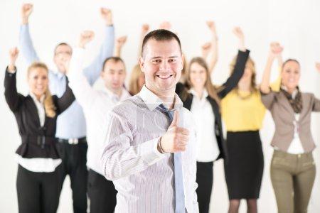 Photo pour Hombre de negocios exitoso mostrando pulgares arriba delante de colegas felices y mirando a la cámara - image libre de droit
