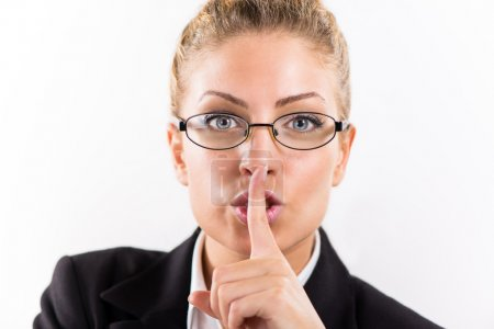 Photo for Portrait of attractive businesswoman with glasses showing shhh. - Royalty Free Image