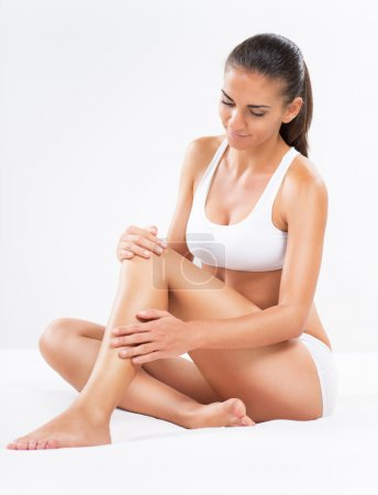 Photo for Beautiful young woman applying body lotion to her legs. - Royalty Free Image