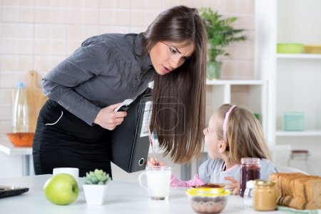 Photo for Overworked Mother Rushing her little daughter in the morning to go faster because she late for work. Daughter having breakfast. Mother and Daughter getting angry with each other because of stress. - Royalty Free Image