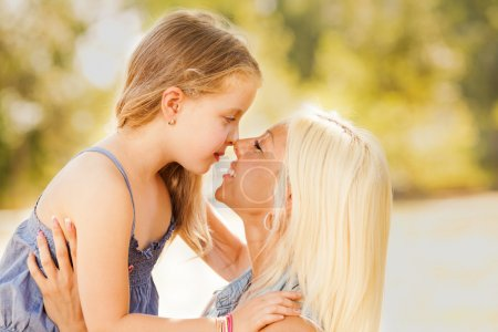 Photo for Beautiful, happy mother and daughter touching noses in the nature - Royalty Free Image