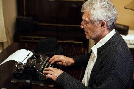Foto de Escritor retro senior hombre con gafas escribir en máquina de escribir obsoleta. - Imagen libre de derechos