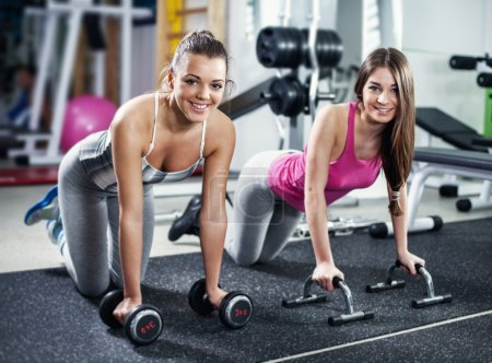 Cute Sporty girls doing exercise in a fitness center. Looking At Camera.
