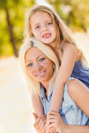Photo for Beautiful, happy mother and daughter hugging in the park - Royalty Free Image