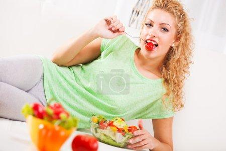 Photo pour Belle jeune femme mangeant petite tomate à la fourchette - image libre de droit