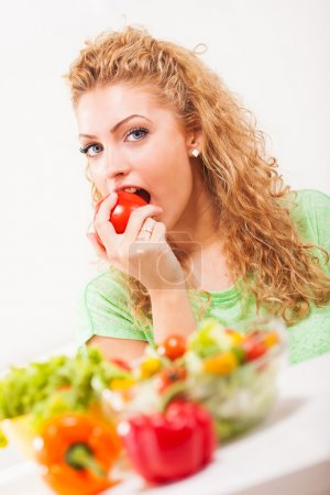 Photo for Beautiful young woman eating tomato - Royalty Free Image