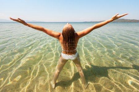 Photo pour Jeune belle femme profitant du soleil et debout dans la mer transparente . - image libre de droit
