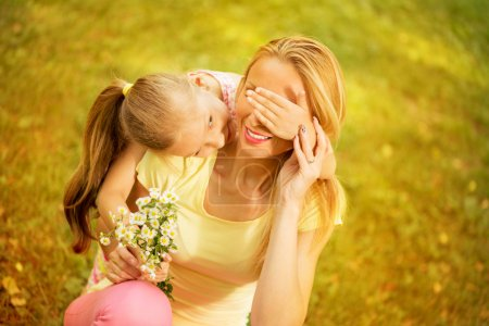 Photo for Cute little girl embraced her mother. She is wants surprise with bouquet flowers - Royalty Free Image