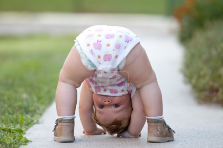 Photo for One-year baby girl playing upside down on the street - Royalty Free Image