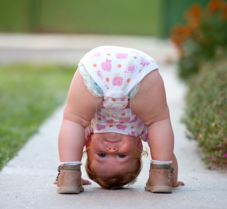 One-year baby girl playing upside down on the stre...