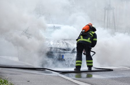 Firefighter is putting out a burning car