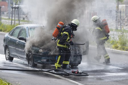 Firefighters are putting out a burning car