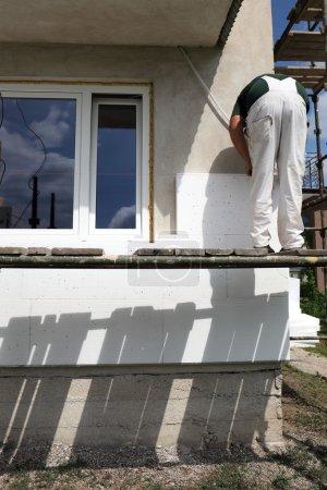 Foto de Trabajador colocación de aislamiento de espuma de poliestireno hoja a la pared - Imagen libre de derechos
